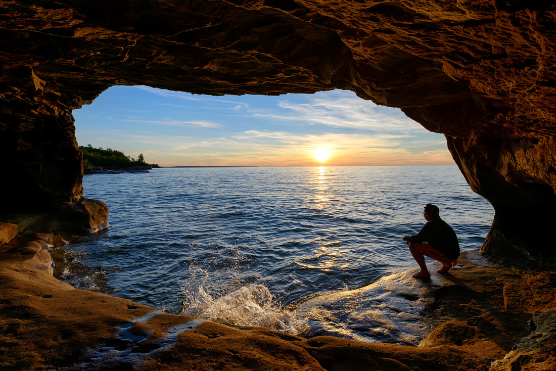 """Person watching a sunset in a sea cave"""